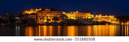 Romantic luxury India travel tourism - City Palace complex on Lake Pichola in twilight, Udaipur, Rajasthan, India - stock photo