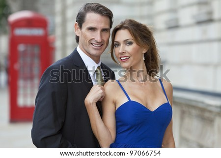 Romantic man and woman couple by a traditional red phone box, London, England, Great Britain - stock photo