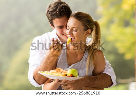 romantic man feeding wife scrambled eggs for breakfast - stock photo