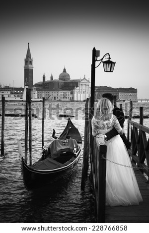 Romantic married couple in Romantic Italian city of Venice in black and white. Traditional Venetian wooden gondola and Roman Catholic church of San Giorgio Maggiore in the background. - stock photo
