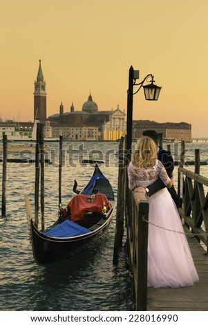 Romantic married couple in Romantic Italian city of Venice in sunset. Traditional Venetian wooden gondola and Roman Catholic church of San Giorgio Maggiore in the background. - stock photo