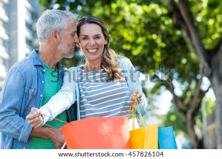 Romantic mature couple holding shopping bags in city