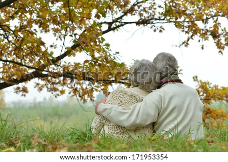 Romantic mature couple is sitting in the park in fall - stock photo