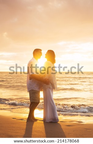 Romantic Mature Couple Kissing at Sunset on the Beach - stock photo