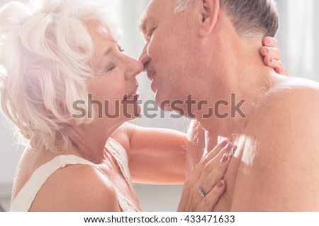 Romantic mature marriage kissing each other, light interior