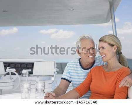 Romantic middle aged couple spending time together on yacht - stock photo