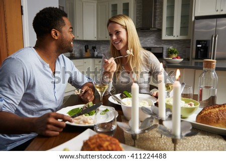 Romantic mixed race couple eating evening meal in kitchen - stock photo
