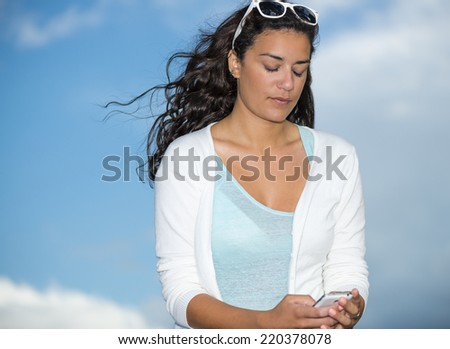 Romantic modern young woman (20s) seems dreaming with wind into long hairs. Closeup head and shoulders with blue sky on copy space background. She is holding her smartphone with eyes closed. - stock photo