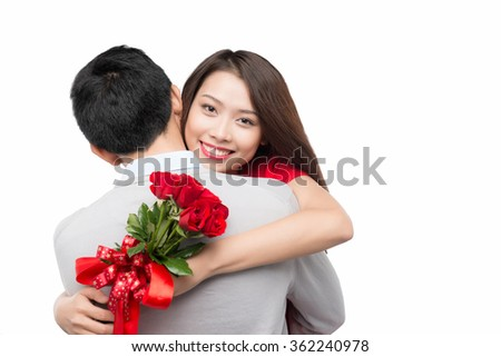 romantic moment: young man giving a rose to his girlfriend. Embracing couple hugging happy. Smiling interracial couple in love isolated on white background. - stock photo