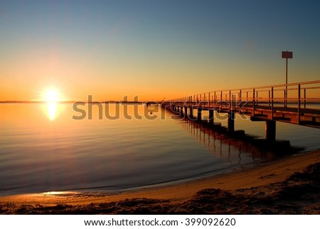 Romantic morning in harbor. Tourists pier construction above sea. Sunny clear blue sky, smooth water level - stock photo