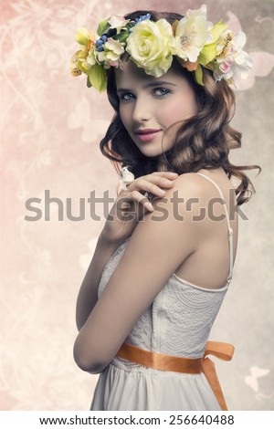 Romantic, natural, pretty brunette woman with wreath of flower and little bird on her finger. She wears white dress and colorful makeup. - stock photo
