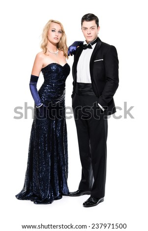 Romantic new year's eve fashion couple wearing black dinner jacket and dark blue dress. Isolated against white. - stock photo
