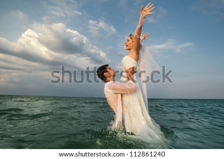 Romantic newly-married couple enjoying a summer vacation. Young groom lifting his bride in sea - stock photo