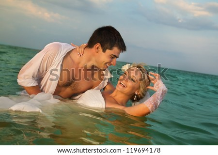 Romantic newly-married couple swimming in sea water
