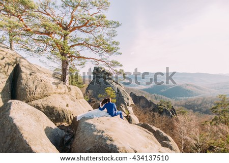 Romantic newlywed couple sitting on cliff with mountain landscape. View from pair's back