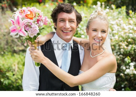 Romantic newlywed couple smiling at camera on their wedding day in the countryside - stock photo