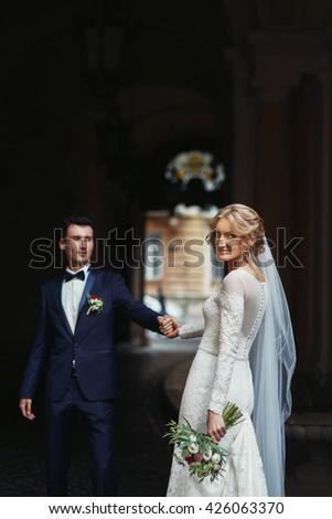 Romantic newlyweds holding hands & posing under arch in street - stock photo