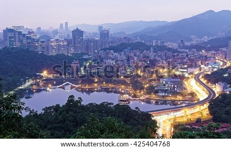 Romantic night aerial view of Da-Hu Community Park at dusk with an oriental arch bridge over the lake and nearby traffic trails on a busy street in Nei-Hu district, Taipei City, Taiwan - stock photo
