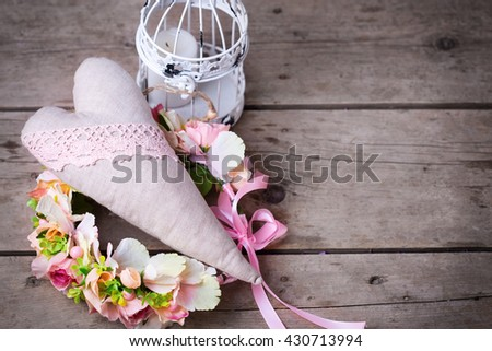 Romantic or wedding background. Flower wreath, decorative heart and decorative lantern with candle on vintage  wooden background. Selective focus. Place for text. - stock photo