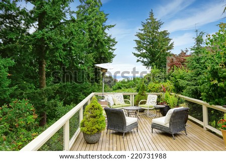 Romantic patio area on walkout deck with bay view. Wicker patio set with heater - stock photo