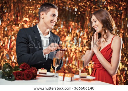 Romantic photo of beautiful couple on glitter gold background. Couple having dinner. There are glasses with champagne, desserts and roses on table. Man proposing to marry him with engagement ring - stock photo