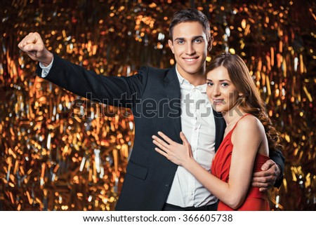 Romantic photo of beautiful couple on glitter gold background. Handsome young man and beautiful woman hugging and looking at camera
