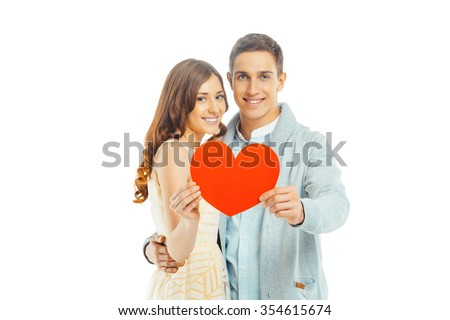 Romantic photo of beautiful couple on white background. Handsome young man and beautiful woman smiling, looking at camera and holding Valentine card in shape of heart - stock photo