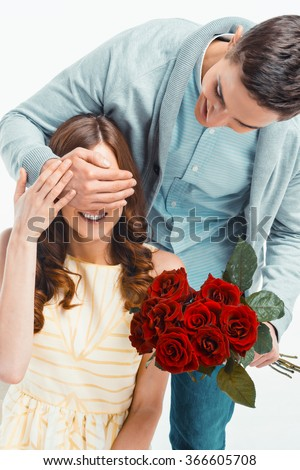 Romantic photo of beautiful couple on white background. Handsome young man giving red roses to his girlfriend and closing her eyes - stock photo