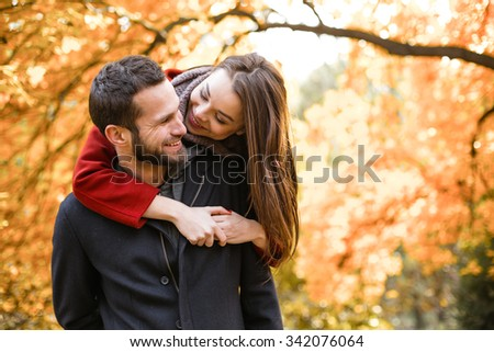 Romantic photo of cute couple outdoors in fall. Young man and woman doing piggyback - stock photo