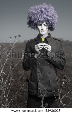 Romantic photo of the clown outdoors holding yellow flower