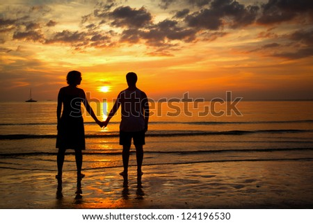 Romantic picture: Silhouettes young couple on the beach at sunset. - stock photo