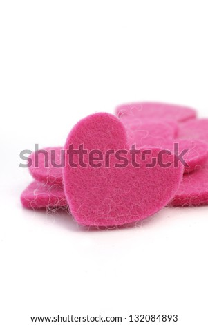 Romantic pink textile hearts with fibre texture in a pile with a single heart facing the camera for a Valentine or anniversary greeting