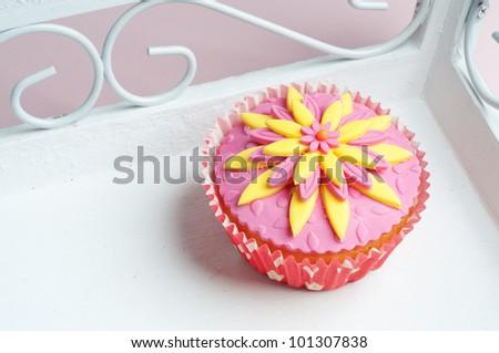 romantic pink yellow flower cupcake - stock photo