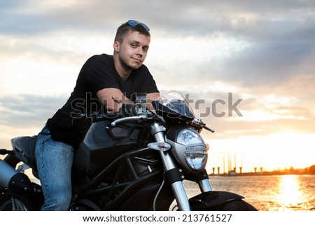 Romantic portrait handsome biker man in sunglasses sits on a bike on a sunset near lake and city