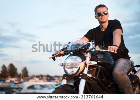 Romantic portrait handsome biker man in sunglasses sits on a bike on a sunset near lake and yacht club. copy space left - stock photo