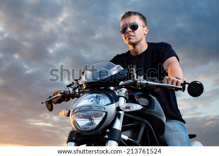 Romantic portrait handsome biker man in sunglasses sits on a bike on a sunset sky background. Copy space left - stock photo