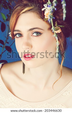 Romantic portrait of a beautiful woman with red hair and flowers in her hairstyle, wearing diamond ear cuff against blue grunge background - stock photo