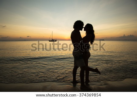 Romantic portrait of attractive couple in love hugs  at the sunset on a tropic island. Against the backdrop of the sea and setting sun. In the distance a boat  in the sea. Silhouette
