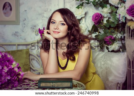 Romantic portrait of beautiful cheerful girl in room with pink flowers and yellow dress - stock photo