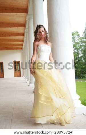 romantic portrait of the dancing bride in white-golden gown near pillars