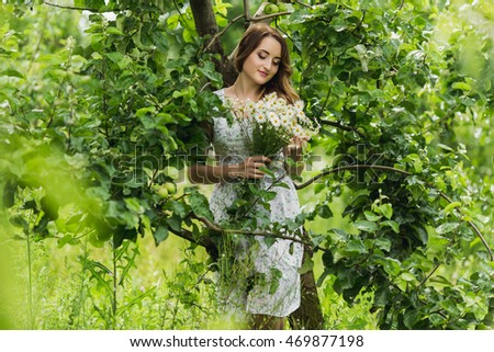 Romantic portrait of young beautiful girl standing at summer park and looking forward.