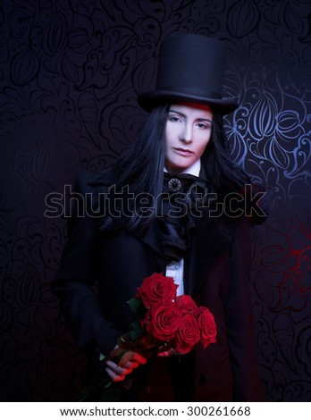 Romantic portrait of young woman in gothic man image posing with red roses