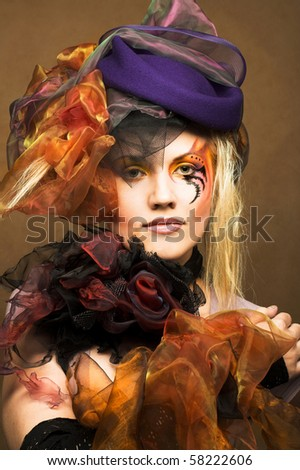 Romantic portrait of young woman with bright creative make-up in fantastic hat - stock photo