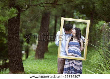 Romantic pregnant couple kissing under pine tree while holding a frame - stock photo