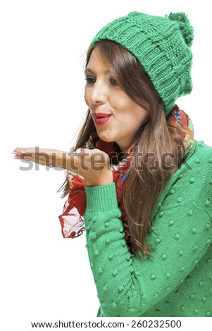 Romantic pretty young woman in a knitted green winter outfit blowing a kiss across the palm of her hand to her sweetheart or while flirting, isolated on white
