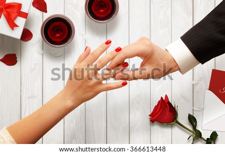 Romantic proposal, wedding or Valentine's Day scene. Man putting engagement ring. Background with glasses of wine, gift, rose, envelope on wooden table. - stock photo