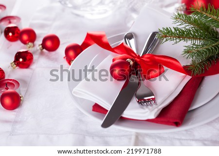 Romantic red Christmas table setting with white plates, red and white linen and silverware tied with a red ribbon and bow decorated with red Xmas baubles and evergreen natural pine foliage - stock photo