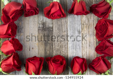 Romantic red rose frame for a special occasions on a wooden background with copy space.
