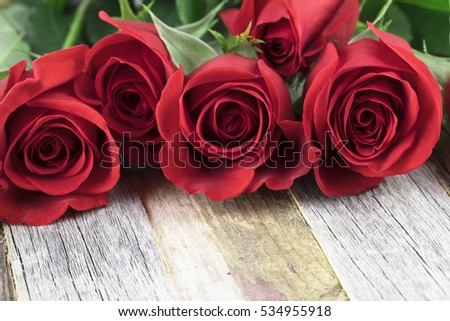 Romantic red roses for a special occasions on a wooden background with copy space.