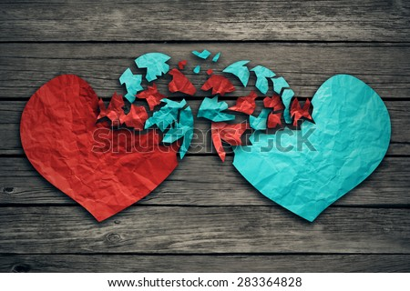 Romantic relationship concept as two hearts made of torn crumpled paper on weathered wood as symbol for romance attachment and exchange of feelings and emotions of love. - stock photo